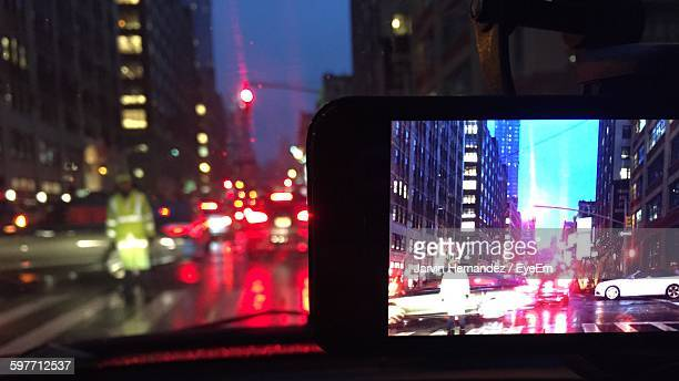 Traffic Cop Standing On Illuminated Traffic In City Seen On Smart Phone In Car