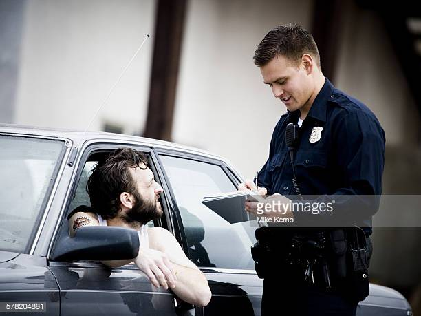 Traffic cop writing ticket to male driver with cigarette