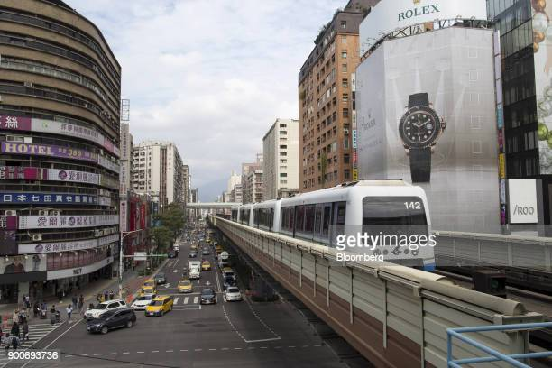 Traffic drives along a road as a Mass Rapid Transit train operated by Taipei Rapid Transit Corp travels along an elevated track in Taipei Taiwan on...