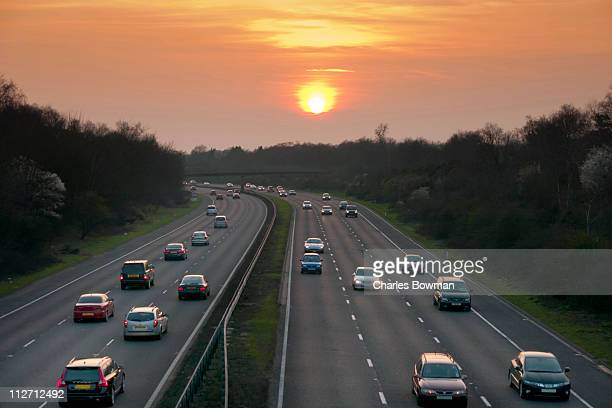 Traffic drives along motorway with sun setting .