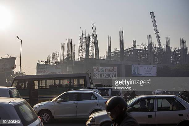 Traffic drives past a construction site shrouded in smog in New Delhi India on Monday Jan 11 2016 A 2judge Delhi High Court panel headed by Chief...