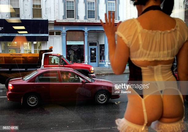 Traffic drives past the window where Nikki Hunt models lingerie in the front of Spellbound, a lingerie store, December 2, 2005 in Augusta, Maine....
