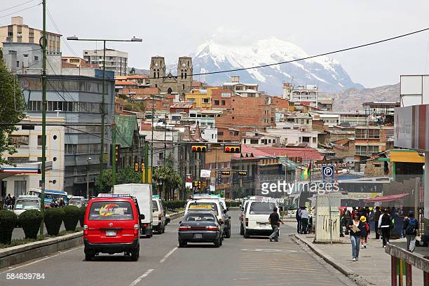Traffic in street downtown La Paz and the snow covered mountain Ilimani Bolivia