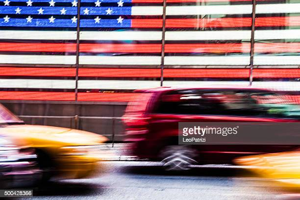 Traffic in Times Square in front of American Flag
