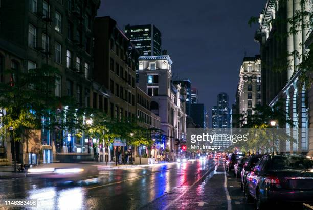 traffic in wet cityscape at night - nightlife stock pictures, royalty-free photos & images
