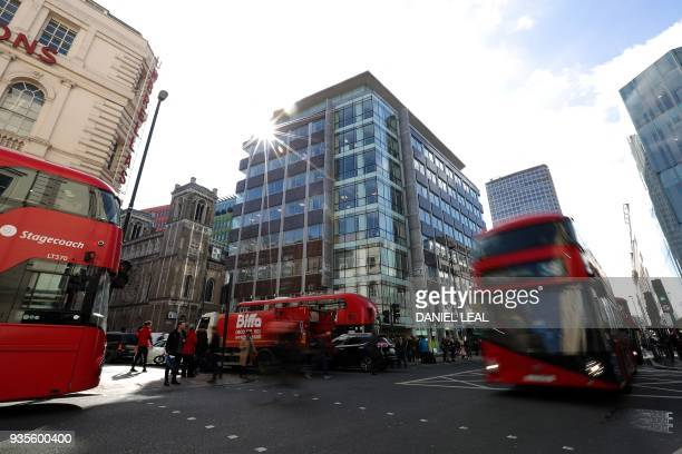 Traffic including red London busses passes the shared building which houses the offices of Cambridge Analytica in central London on March 21 2018...