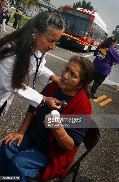 Traffic is blocked during a protest as Patricia Lopez left tends to patient Esther Ceron in the middle of an intersection Wednesday afternoon in East...