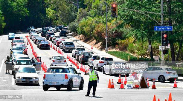 Traffic is directed at Dodger Stadium as people arrive for COVID-19 testing on June 30, 2020 in Los Angeles, California. - The US will start...