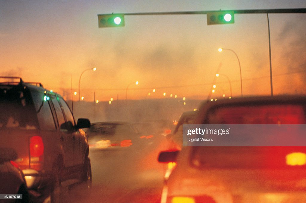 Traffic jam in early evening with exhaust : Stock Photo