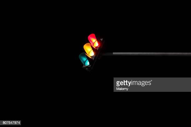 Traffic light at night, close-up, black background
