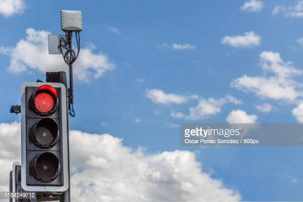 traffic light illuminated in red, with a lovely sky background - semaphore stock pictures, royalty-free photos & images