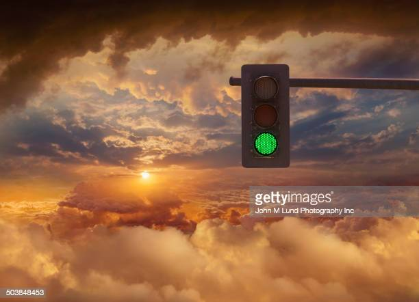 Traffic light in sunset sky