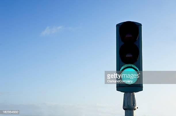 Traffic Light On Green For Go Isolated Against Blue Sky