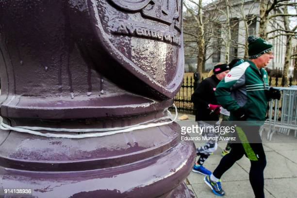 A traffic light pole is seen greased by Philadelphia Police officers as security measure for Super Bowl LII fans while people jog on along Board...
