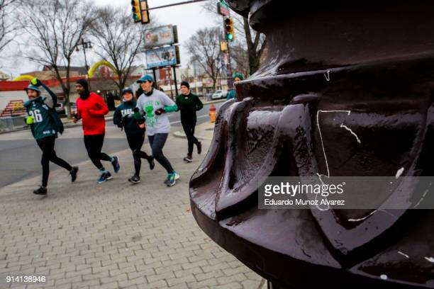 A traffic light pole is seen greased by Philadelphia Police officers as a security measure for Super Bowl LII fans while people jog on along Board...