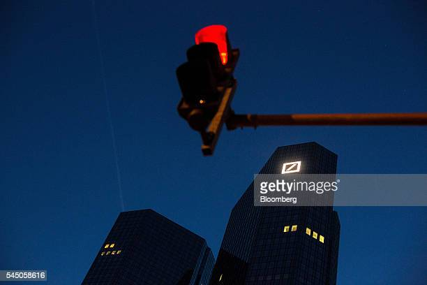 A traffic light signals red as the Deutsche Bank AG logo sits illuminated on the bank's headquarter offices as they stand at night in the financial...