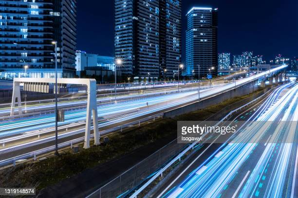 traffic light trails and illuminated buildings at tokyo waterfront area - isogawyi stock pictures, royalty-free photos & images