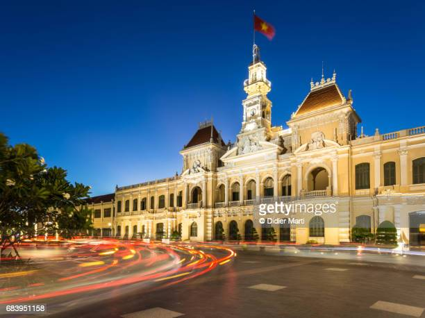 traffic light trails in front of the people's comittee building in ho chi minh city - people's committee building ho chi minh city stock pictures, royalty-free photos & images