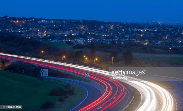 Traffic light trails on the A27 dual carriageway against a backdrop of residential houses at dusk in Brighton, U.K., on Thursday, Nov. 12, 2020....