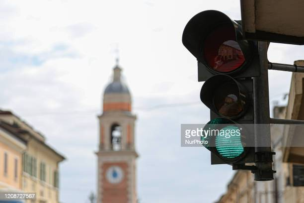 Traffic light with green light in the background the bell tower of the municipality of Rolo during COVID19 pandemic in Italy on March 31 2020 in Rolo...