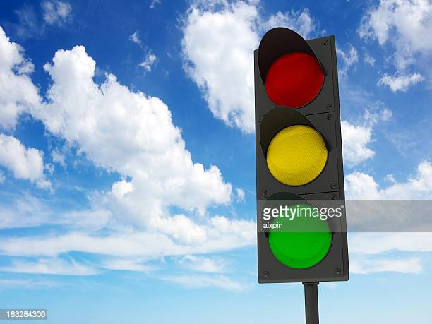 Traffic lights against the blue cloudy sky