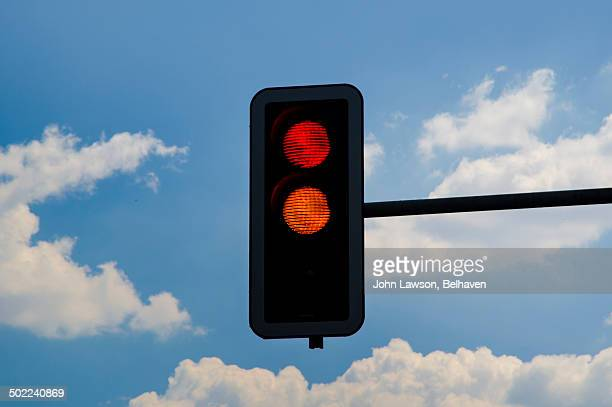 Traffic lights red and amber against blue sky