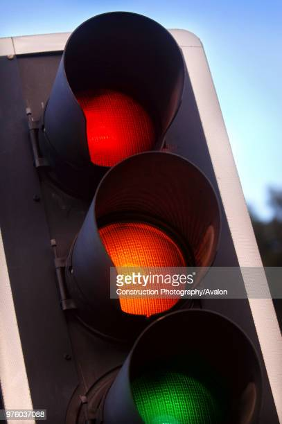 traffic lights showing amber red and green at a crossroads UK