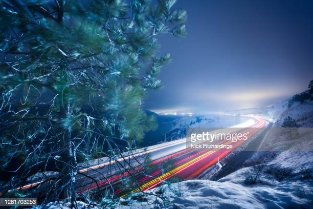 traffic lights streaming along the highway in winter, okanagan valley, british columbia, canada - thompson okanagan region british columbia stock pictures, royalty-free photos & images