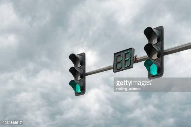 traffic lights under the dark clouds - semaphore stock pictures, royalty-free photos & images
