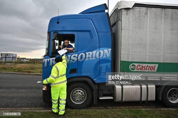 Traffic marshall checks the documents of a freight lorry driver at Waterbrook Park facility in Ashford, south east England on January 15 as hauliers...