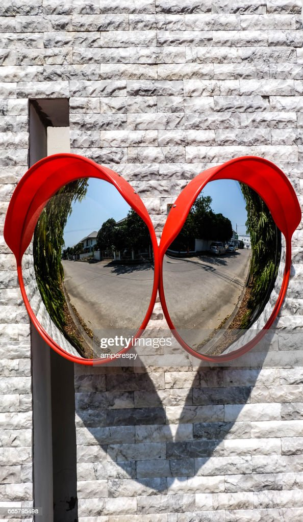 Traffic mirror on the wall at intersection or curve of road, safety and security concept, close up : Stock Photo