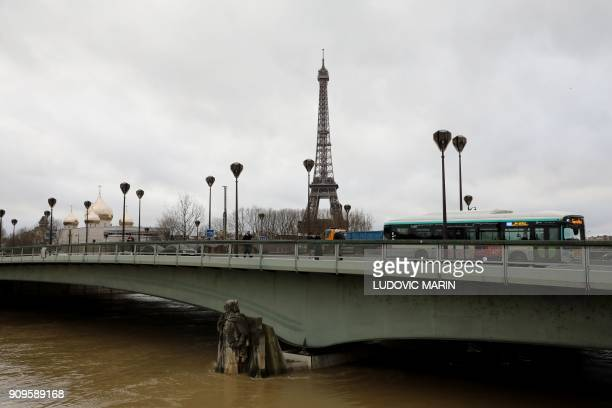 Traffic moves across the Pont D'Alma bridge past the Eiffel Tower and the Holy Trinity Cathedral as the Zouave statue stands partially submerged...