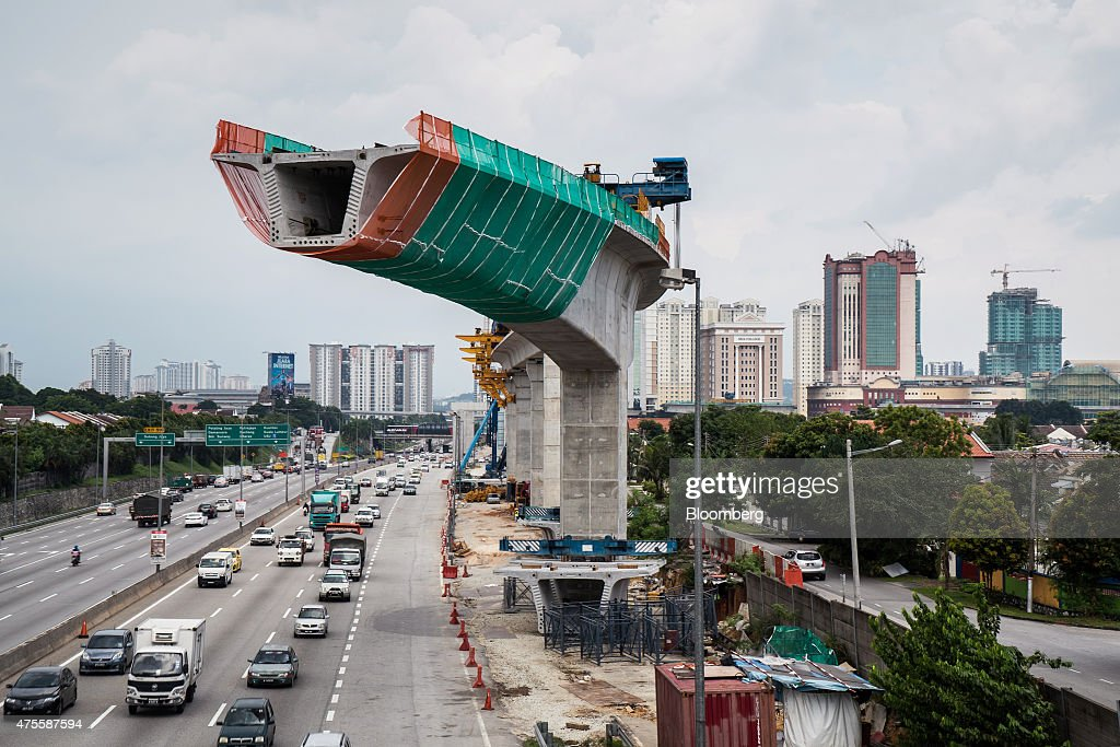 Traffic moves along a highway under the ongoing construction of an overhead rail track in Subang, Selangor, Malaysia, on Wednesday, May 27, 2015. Malaysia's ringgit fell for a sixth day on June 1, in the longest stretch of losses since 2013 as falling oil prices weigh on the nation's finances. Photographer: Sanjit Das/Bloomberg via Getty Images