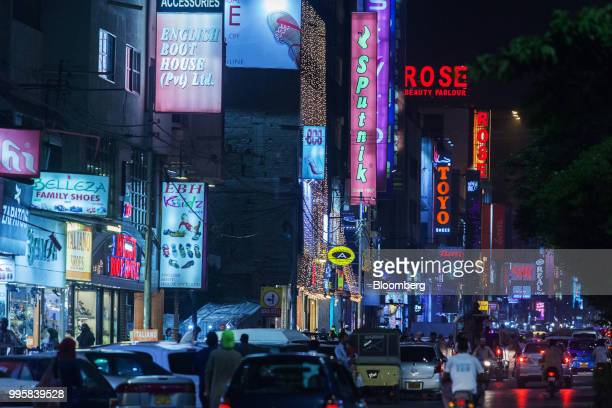 Traffic moves along a road as shop signs stand illuminated at night in Karachi Pakistan on Monday July 9 2018 The Pakistan economy is in distress How...