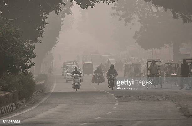 Traffic moves along a street amid heavy dust and smog November 7 2016 in Delhi India People in India's capital city are struggling with heavily...