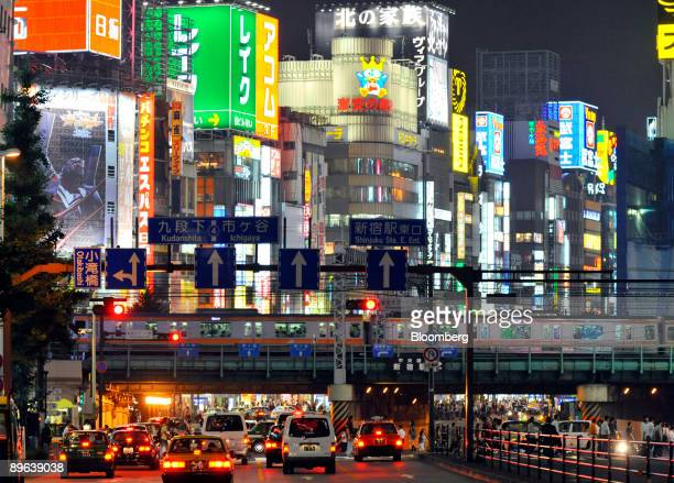 Traffic moves along a street in front of buildings illuminated by neon signs in the Shinjuku district of Tokyo Japan on Thursday July 2 2009 Japan's...