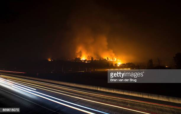 Traffic moves along the 101 Freeway in Santa Rosa as the Hilton Hotel continues to burn on October 9 2017 in Santa Rosa California