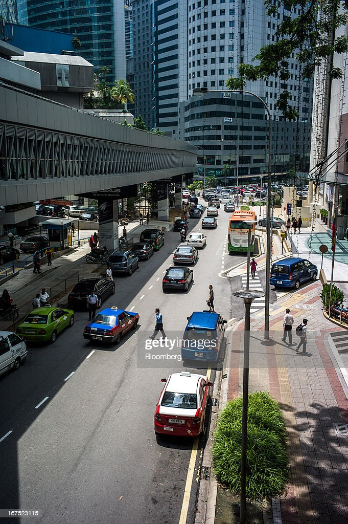 Traffic moves down the street as pedestrians cross in Kuala Lumpur, Malaysia, on Thursday, April 25, 2013. Malaysians will go to the polls on May 5. Prime Minister Najib Razak's National Front coalition is seeking to extend its 55 years of unbroken rule in the face of a resurgent opposition led by Anwar Ibrahim. Photographer: Sanjit Das/Bloomberg via Getty Images