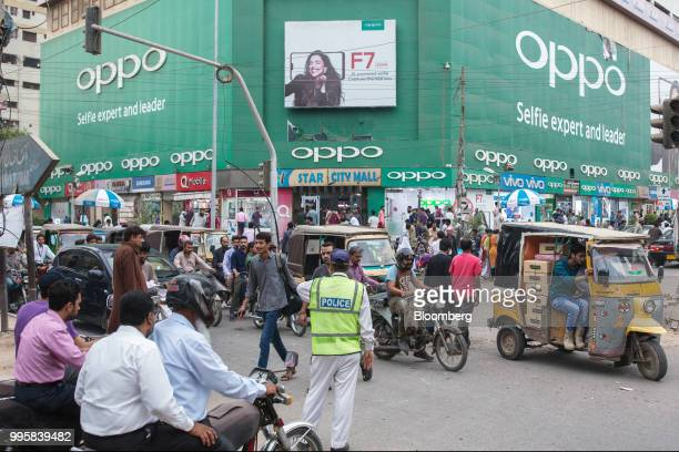 Traffic moves in front a store displaying signage for GuangdongOppoElectronics Co at the Karachi Mobile Market in Karachi Pakistan on Monday July 9...