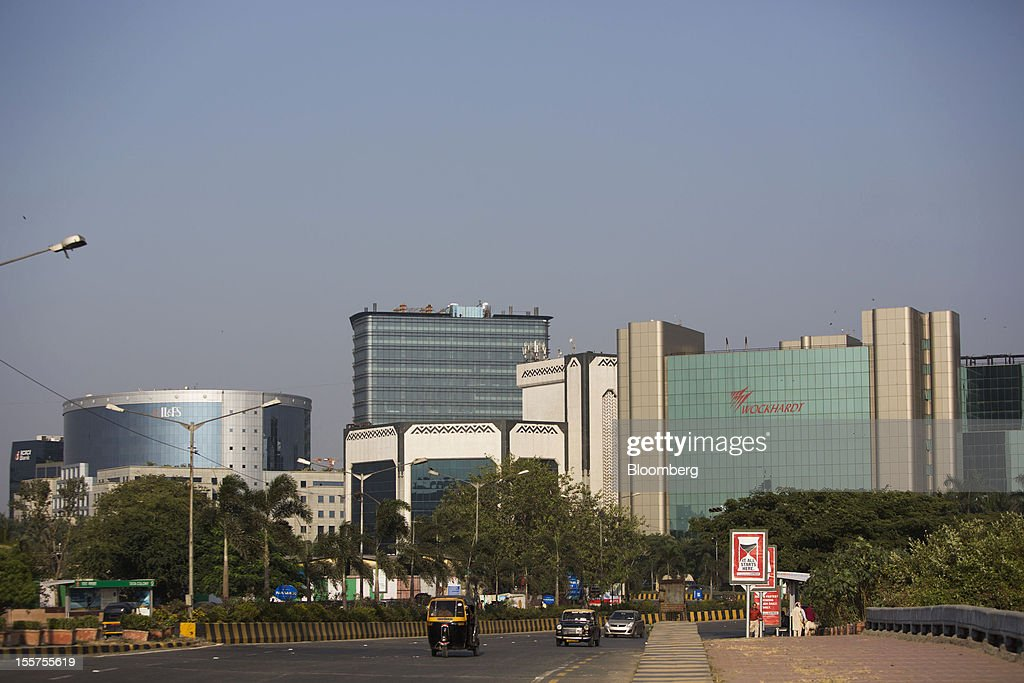 Traffic moves in front of the Wockhardt Ltd. headquarters, right, in the Bandra Kurla Complex in Mumbai, India, on Tuesday, Nov. 6, 2012. Reserve Bank of India Governor Duvvuri Subbarao lowered the RBI's forecast for India's gross domestic product growth in the year through March to 5.8 percent, the slowest in almost a decade, from 6.5 percent. Photographer: Brent Lewin/Bloomberg via Getty Images