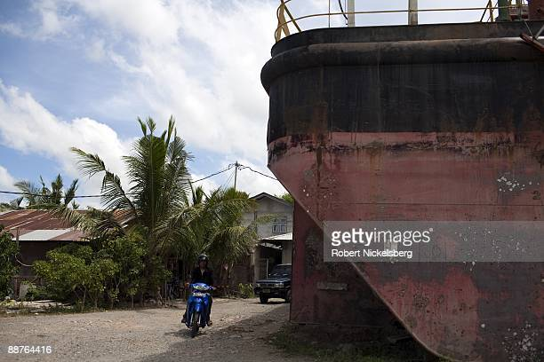 Traffic moves past a floating generator barge lying aground in a Banda Aceh neighborhood after it was carried 6 kms inland during the December 26...