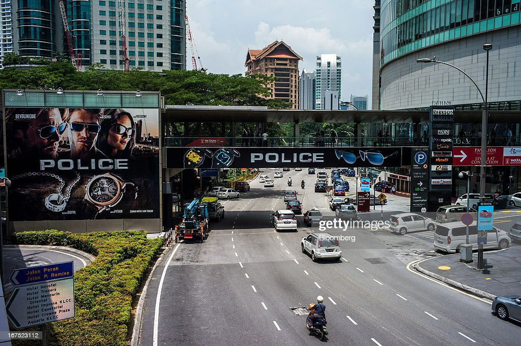 Traffic moves past the Pavilion Mall shopping center as an advertisement for De Rigo Group SpA Police brand products is displayed on the side of the Mall in Kuala Lumpur, Malaysia, on Thursday, April 25, 2013. Malaysians will go to the polls on May 5. Prime Minister Najib Razak's National Front coalition is seeking to extend its 55 years of unbroken rule in the face of a resurgent opposition led by Anwar Ibrahim. Photographer: Sanjit Das/Bloomberg via Getty Images