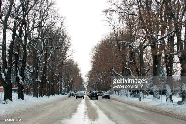 Traffic navigates snow packed and icy roads in Denver Colorado on November 27 2019 A pair of storms packing heavy snow and hurricaneforce winds left...