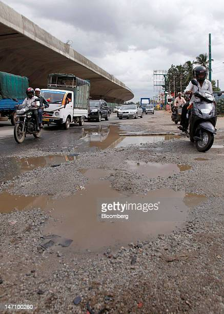 Traffic navigates through pot holes on National Highway 7 in Bangalore India on Friday June 22 2012 The city's traffic jams make it the sixthmost...