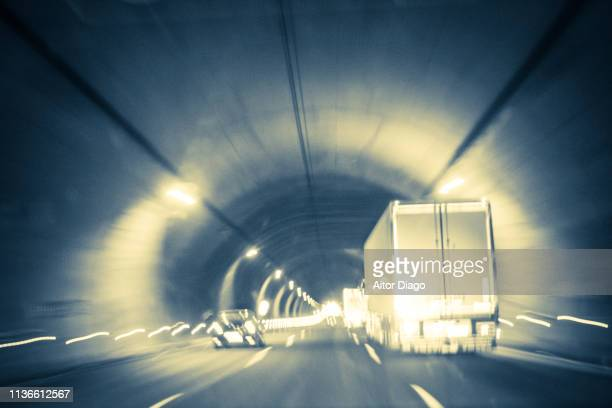 Traffic of trucks and cars through a tunnel. Image moved and with a retro style