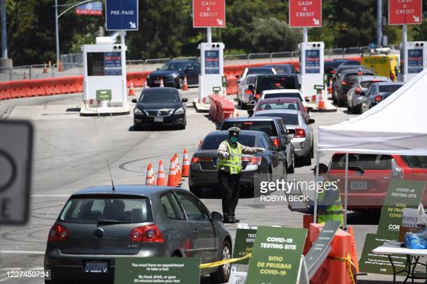 Traffic officer directs cars at a drive-through COVID-19 test site, July 15, 2020 at Dodgers Stadium in Los Angeles, California. - Los Angeles County...