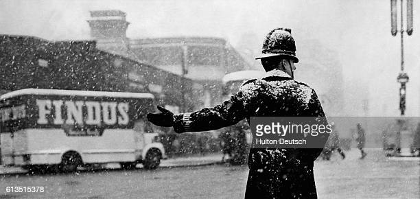 A traffic officer directs traffic around Ludgate Circus in the snowfall