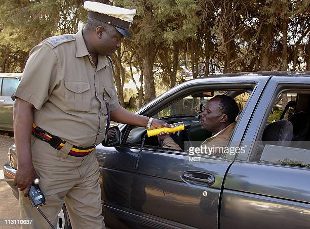 Traffic officer Muli checks a driver driver in Nairobi Kenya with a breathalyzer at a traffic checkpoint Use of the device is rare in African...