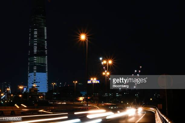 Traffic on a flyover passes the under construction Exchange 106 building left on the site of the Exchange TRX precinct at night in Kuala Lumpur...