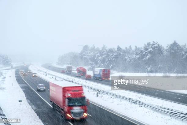 traffic on a highway during a snow blizzard in winter - road salt stock pictures, royalty-free photos & images